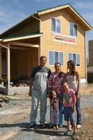 многодетная семья на фоне собственного каркасно-панельного дома
